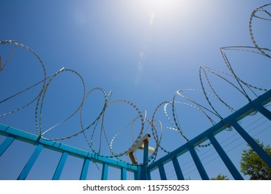 Barbed wire fencing. Blue Fence made of wire with spikes on top to prevent area from dangerous outsider