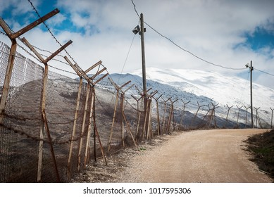 Barbed wire on fence around Israeli settlements on Golan heights, Israel. Border between Palestinian and Israeli territory. Protective fencing of specially protected object of barbed wire.