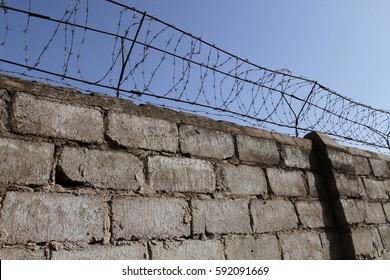 Barbed wire on top of the brick wall restricts the freedom of movement of people and protects the inviolability of private property.