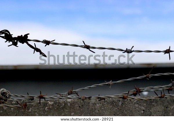 Barbed wire on top of high wall.