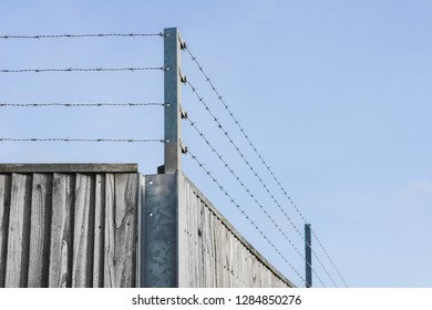 Barbed wire on the top of a wooden fence