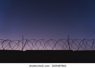 barbed wire prison wall. sunset panorama