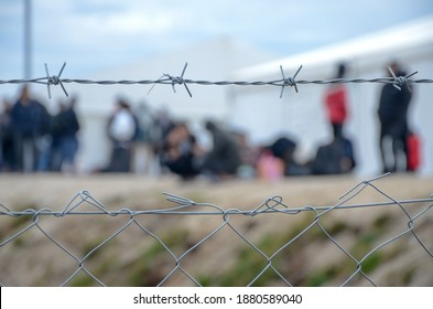 Barbed wire in refugee camp. Migrants behind chain link fence in camp. Group of people behind fence. Concept of prison, freedom, barrier, security and migration. Refugees on their way to EU.