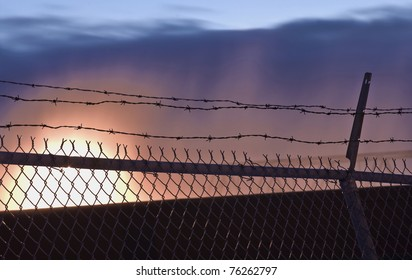 Barbed-wire fence in front of spectacular sunset.