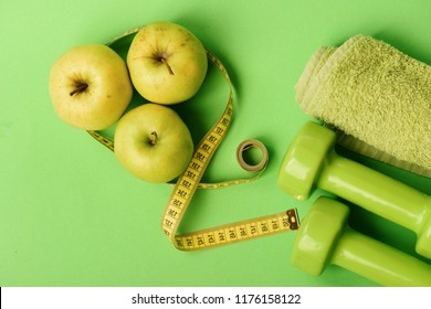 Barbells by juicy green apples. Diet and sport regime concept. Dumbbells in bright green color, twisted measure tape, towel and fruit on green background. Sport and healthy life equipment, copy space.