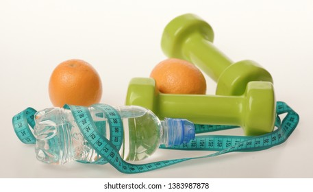 Barbells made of plastic by juicy oranges. Healthy lifestyle and low calorie food concept. Dumbbells in green color, water bottle, measure tape and fruit on white background. Sports and healthy regime