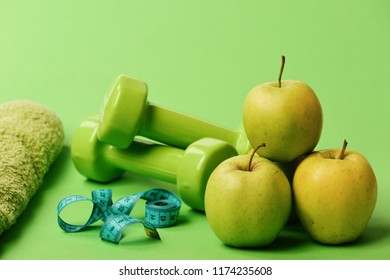Barbells near juicy green apple. Sports and healthy regime equipment, close up. Dumbbells in bright color, rolled measure tape, towel and fruit on green background. Athletics and weight loss concept