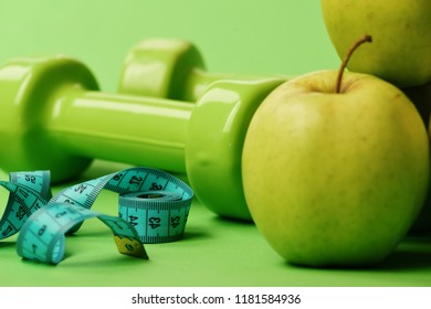 Barbells near juicy green apple. Dumbbells in bright green color, rolled measure tape and fruit on green background. Sports and healthy regime equipment, close up. Athletics and weight loss concept