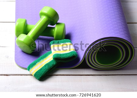 e7a2b5907473b Sport and healthy lifestyle concept. Dumbbells made of green plastic on  light wooden background. Shaping and fitness equipment - Image