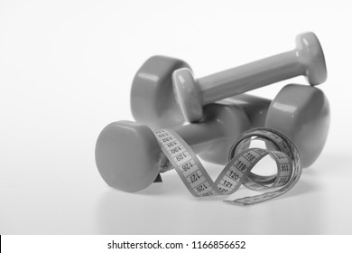 Barbells next to cyan measure tape, close up. Fit shape and sport concept. Health regime and fitness symbols. Dumbbells made of green, blue and pink plastic and rolled ruler on white background.