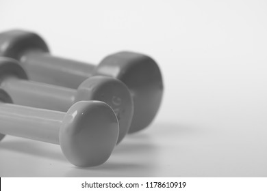 Barbells in pink, green and blue colors, close up. Healthy lifestyle concept. Dumbbells made of plastic put in pattern on white defocused background, copy space. Sport regime and fitness symbols
