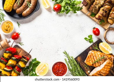 Barbeque dish assortment. Grilled meat, fish, sausages and vegetables. Top view on white stone table.