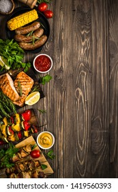 Barbeque dish assortment. Grilled meat, fish, sausages and vegetables. Top view on wooden table.