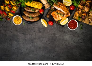 Barbeque dish assortment. Grilled meat, fish, sausages and vegetables. Top view on black background with space for text.