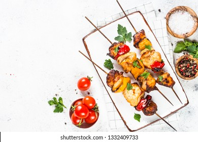Barbeque dish. Chicken kebab or shashlik with vegetables on white stone table. Top view with copy space.