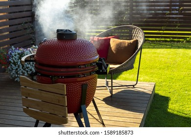Barbeque grill and rattan armchair in cozy home terrace. Smoke coming out of red ceramic Barbeque.