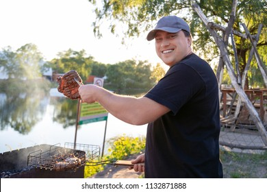 Barbeque party near lake or river outdoors. Man grilling meat beaf steak on open fire brazier. Summer vacation and bbq