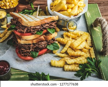 Barbeque pulled beef sandwich, toast, french fries, sauce, corn on a wooden tray
