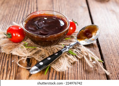 Barbeque Sauce with Tomatoes, Smoked Salt and fresh Herbs (on rustic wooden background)