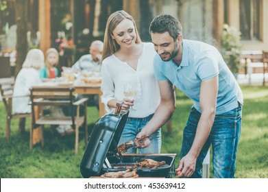 Barbeque time. Happy young couple barbecuing meat on the grill while other members of family sitting at the dining table in the background