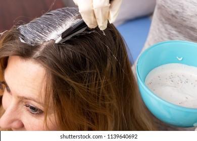 A barber applying hair dye