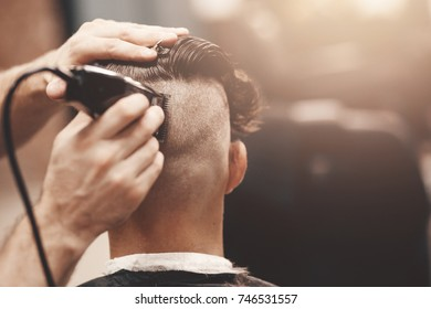 Barber in Barbershop shear hair electric car to young guy hipper for fashionable hairstyle.