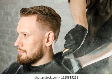 The barber cleans the neck of an adult man  with a brush with talc after a haircut on a white brick wall background
