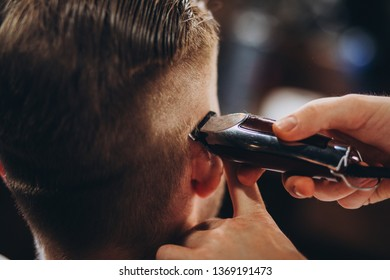 Barber and client during beard shaving and haircut in a classic barber shop
