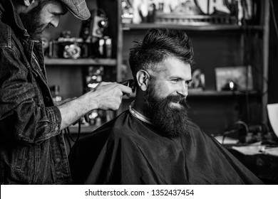 Barber with clipper trimming hair on nape of client. Barber with hair clipper works on haircut of bearded guy barbershop background. Hipster client getting haircut. Hipster hairstyle concept.