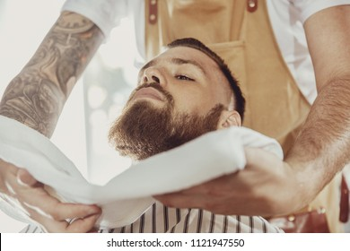 Barber covers the face of a man with a beard with a hot towel. Photo in vintage style