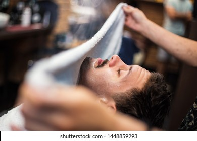 Barber covers the face of a man with a hot towel. Traditional ritual of shaving the beard with hot and cold compresses in a old style barber shop. Hot towel on face before shaving in barber shop
