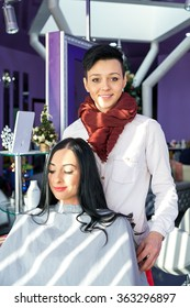 The barber and the customer during operation. Professional. Beautiful young girl in a beauty salon. Doing make-up. Tools hairdresser. A girl with long black hair in a barber chair. Purple background.