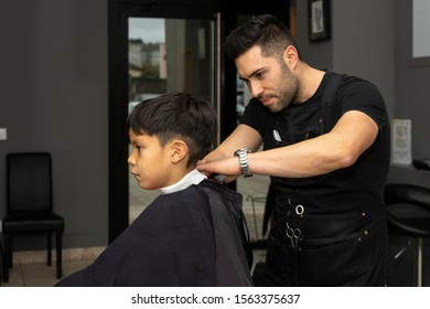 Barber cuts hair to a child in the barber shop