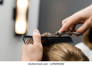 Barber cuts the little blond boy with scissors and combs in the hair salon close-up