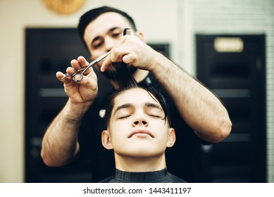 Barber cuts a young guy.