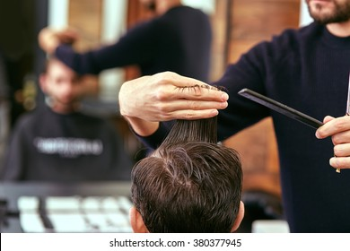 barber cutting hair with scissors. back view of man in barber shop.