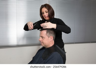 Barber cutting hair with scissors and comb, using cosmetic in spray, client is a  caucasian man