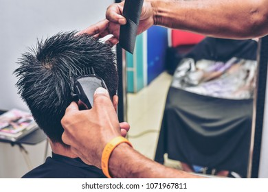 Barber cutting teenager hair with clipper.Man's grooming trimmer in a beauty salon.Hair dressing concept.