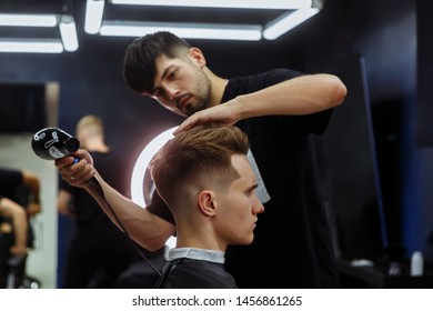 Barber drying male hair in hairdressing salon
