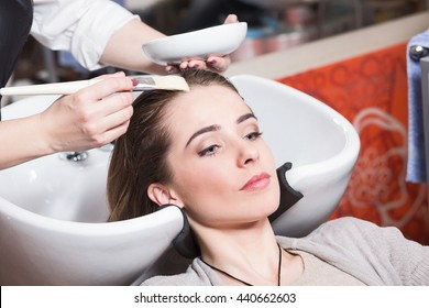 Barber girl combing her hair in beauty saloon. Beautiful lady having her hair washed by hairdresser in hairdressing saloon.