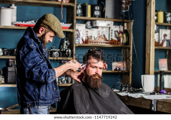 Barber with hair clipper works on hairstyle for bearded man barbershop background. Barber with clipper trimming hair on temple of client. Hipster lifestyle concept. Hipster client getting haircut.