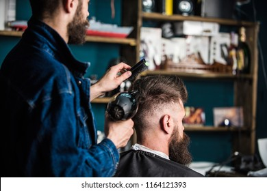 Barber with hairdryer drying and styling hair of client. Barber with hairdryer works on hairstyle for bearded man, barbershop background. Styling concept. Hipster bearded client getting hairstyle.