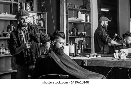 Barber with hairdryer works on hairstyle for bearded man barbershop background. Barber with hairdryer drying hair of client. Hipster lifestyle concept. Hipster bearded client getting hairstyle.