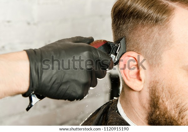 Barber hand in gloves cut hair and shaves adult gihger bearded man on a brick wall background. Close up portrait of a guy