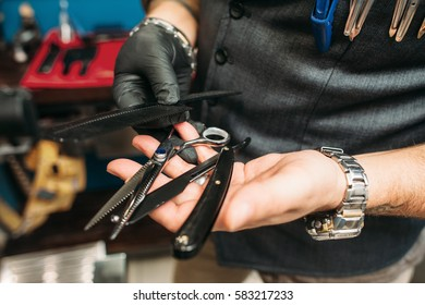 Barber instruments in hands closeup. Professional haircut tools - scissors, razor and hairbrush - in stylist hands, free space. Work, occupation, beauty, barbershop concept