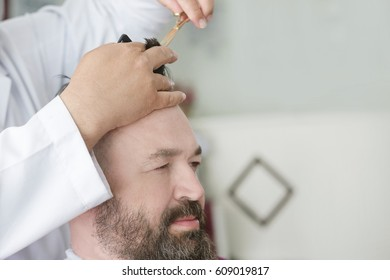 Barber makes a mohawk hairstyle of a adult bearded man