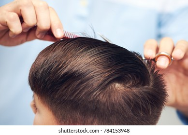 Barber is making haircut to boy in barbershop.  Close view.