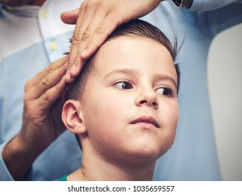 Barber is making a hairstyle to Caucasian boy in barbershop.