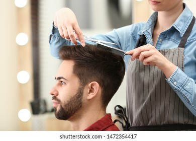 Barber making stylish haircut with professional scissors in beauty salon