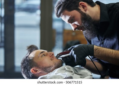 The Barber man in the process of cutting a mustache client electric clippers in the barbershop